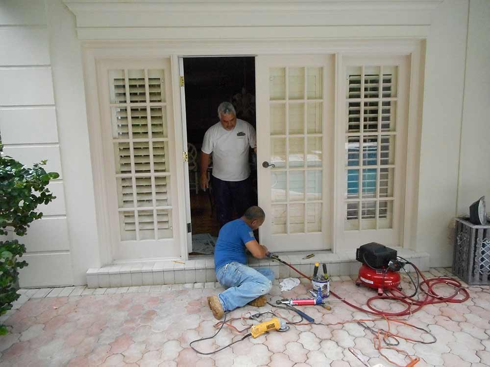 Handyman repairing  a set of french doors for a residential client.